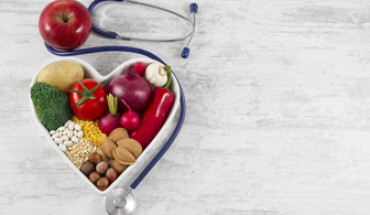 Heart health, and cholesterol diet concept.  Healthy foods in heart shaped bowl with stethoscope and red apple on white vintage wooden table.